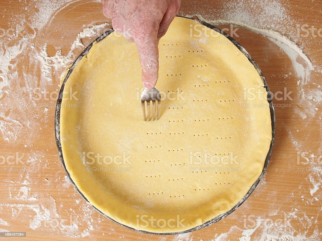 Prick base of pastry case all over with a fork stock photo