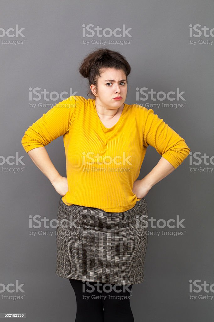 pride and arrogance for offended big young woman standing up stock photo