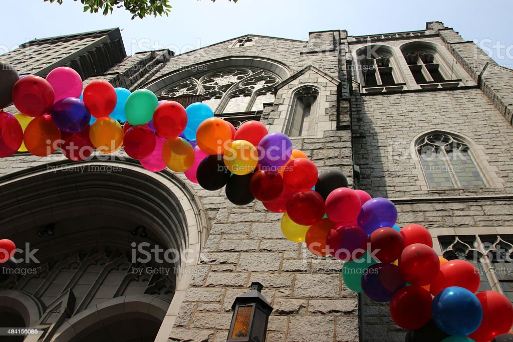 Pride rainbow baloons in front of a church enterance stock photo