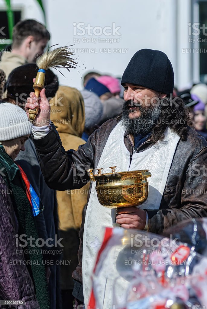 Priest blessing people with holy water. Tyumen stock photo