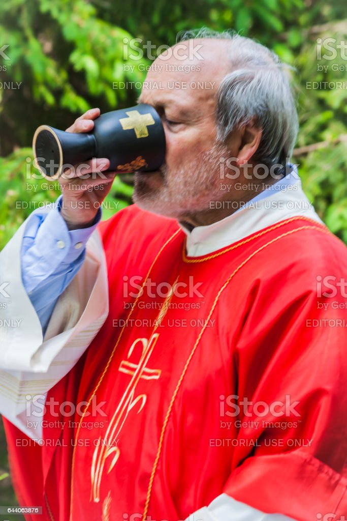Priest drinks wine from sacred chalice stock photo