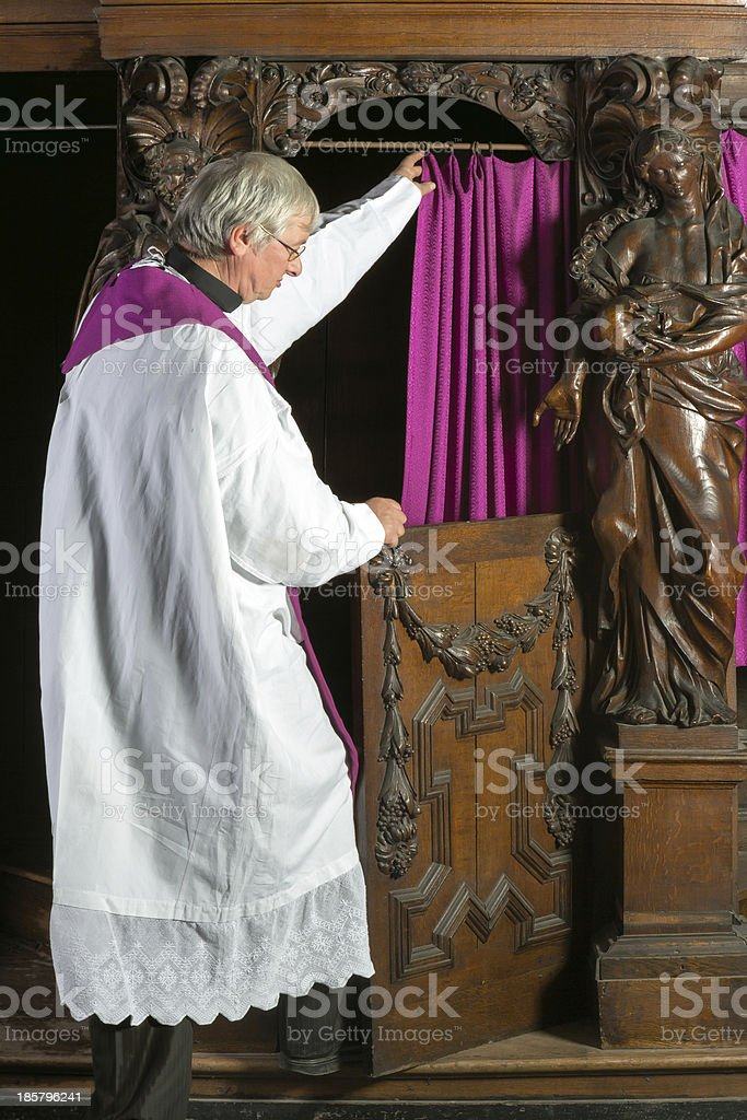 Priest entering confession booth royalty-free stock photo