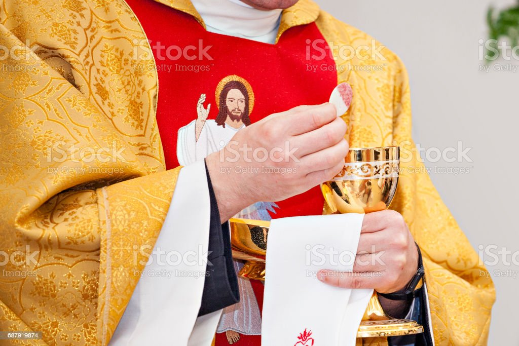Priest gives communion. A host laden with wine. Symbol of the body and blood of Christ. stock photo