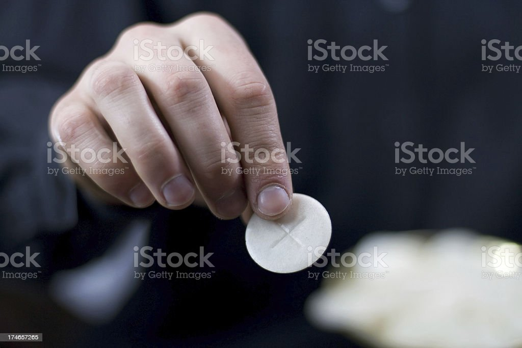 Priest gives communion stock photo