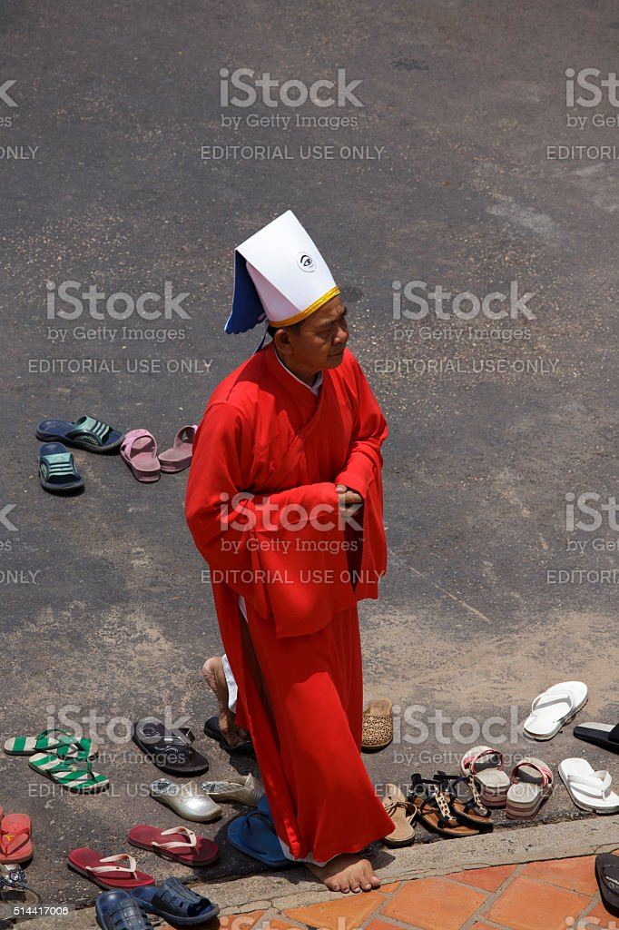 Priest going in a Caodai temple in Vietnam stock photo