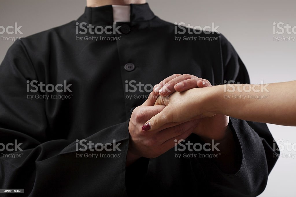 Priest holding believer hand stock photo