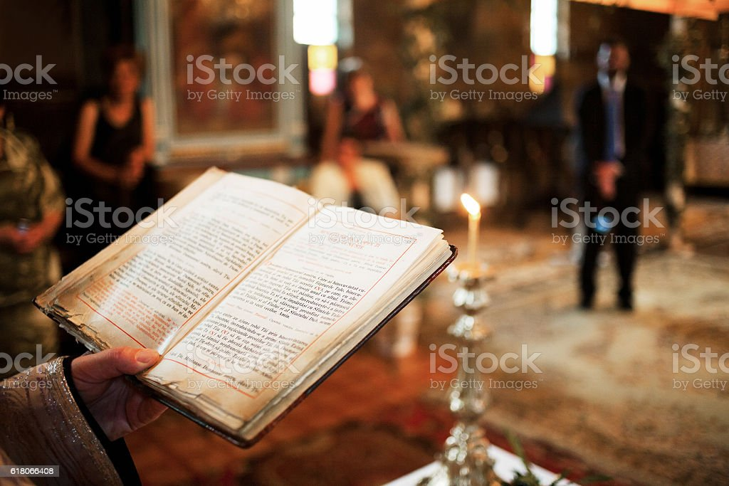 Priest holding bible in church stock photo