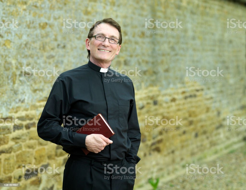 Priest holding Bible stock photo