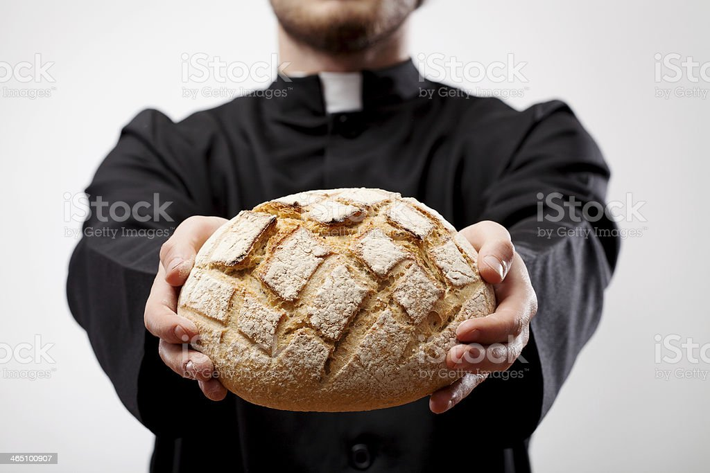 Priest holding loaf of bread stock photo