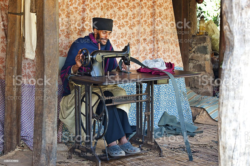 Priest in a monastery with sewing machine, Lake Tana, Ethiopia stock photo