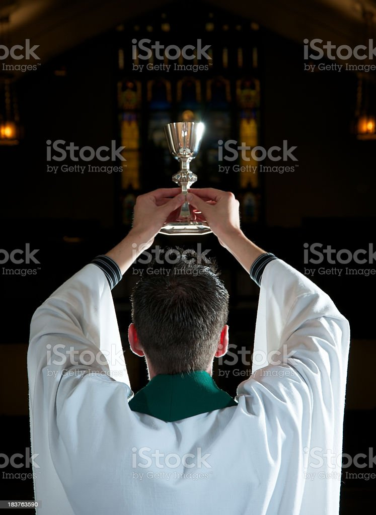 Priest in Robe Blessing Wine for Communion stock photo