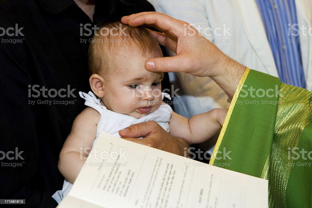 Priest is baptizing little baby in church. stock photo