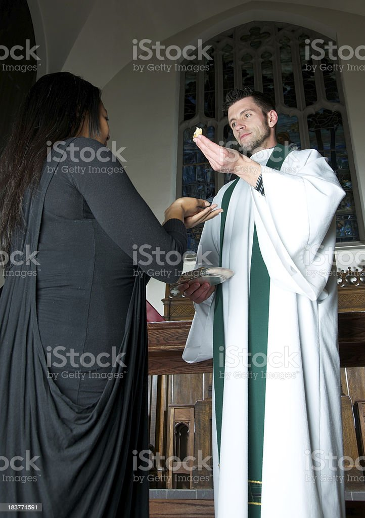 Priest Offering Communion Bread to Hawaiian Woman stock photo