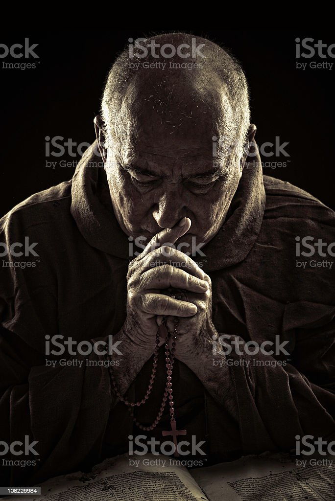 priest praying stock photo