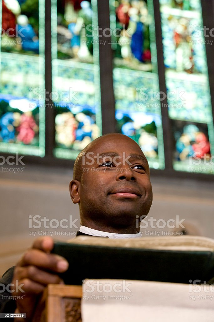 Priest Reading from Bible on Church Altar stock photo