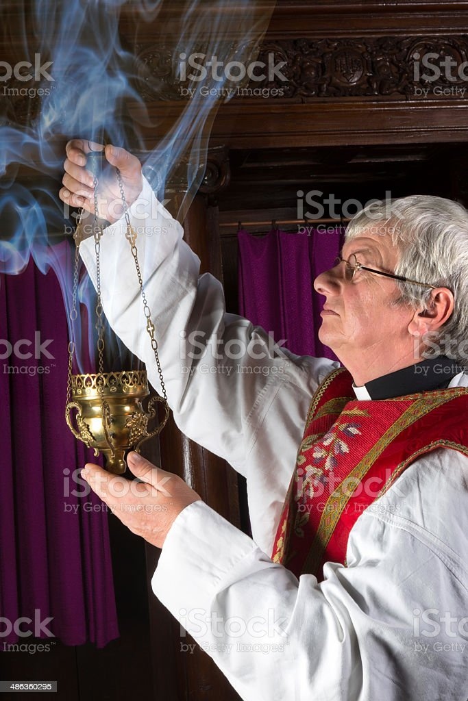 Priest with incense burner stock photo