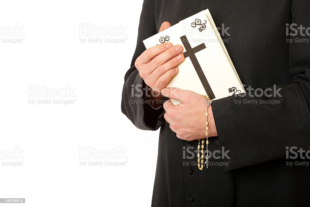 Priest's hands on bible with rosary stock photo