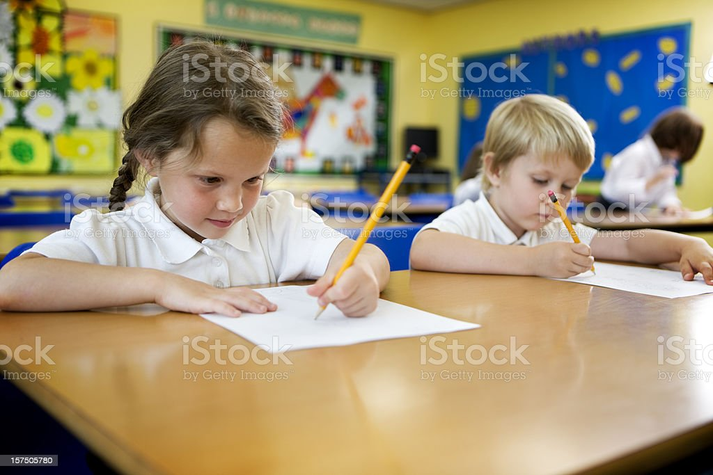 Primary school Children sitting at their desk's and working stock photo