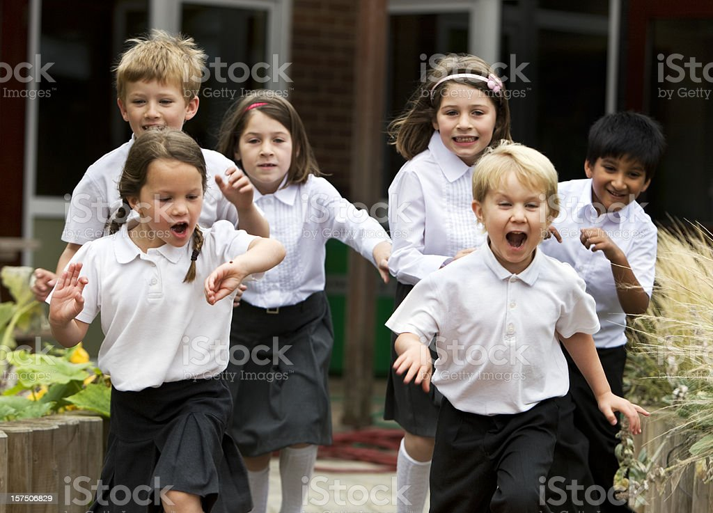 primary school: delighted and excited junior school children leaving class stock photo