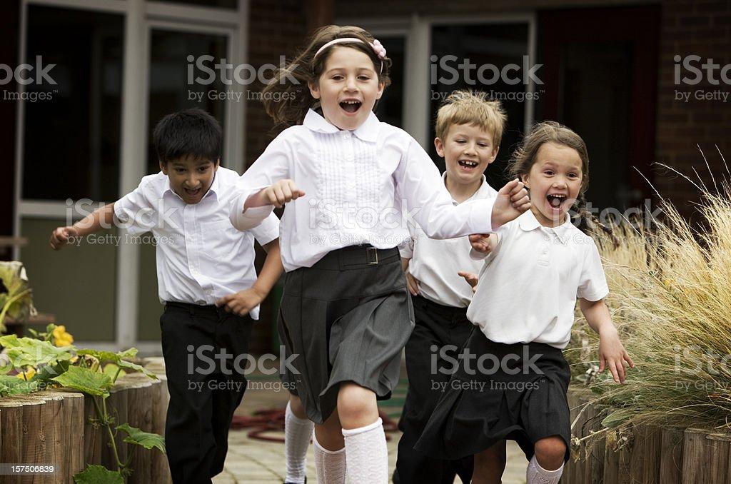 primary school: junior school children running out of their school stock photo