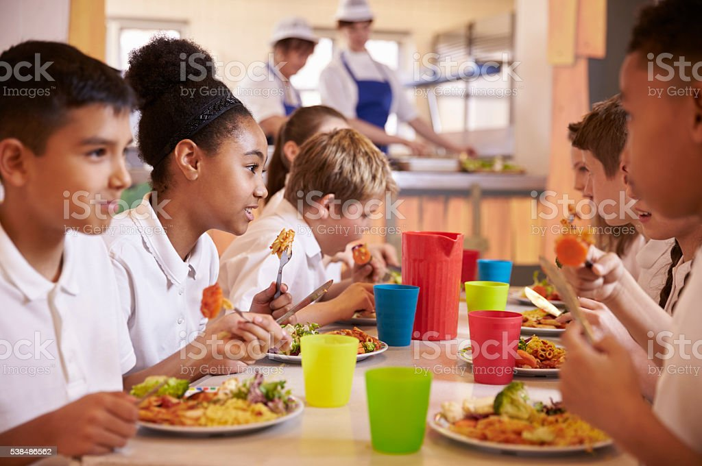 Primary school kids eat lunch in school cafeteria, close up stock photo