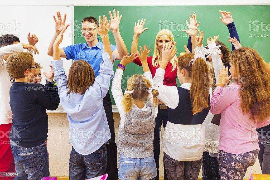 Primary school kids in classroom with two teachers having fun stock photo