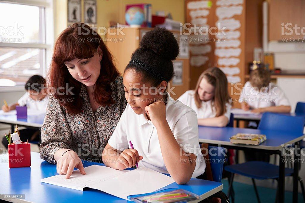Primary school teacher helping a schoolgirl at her desk stock photo