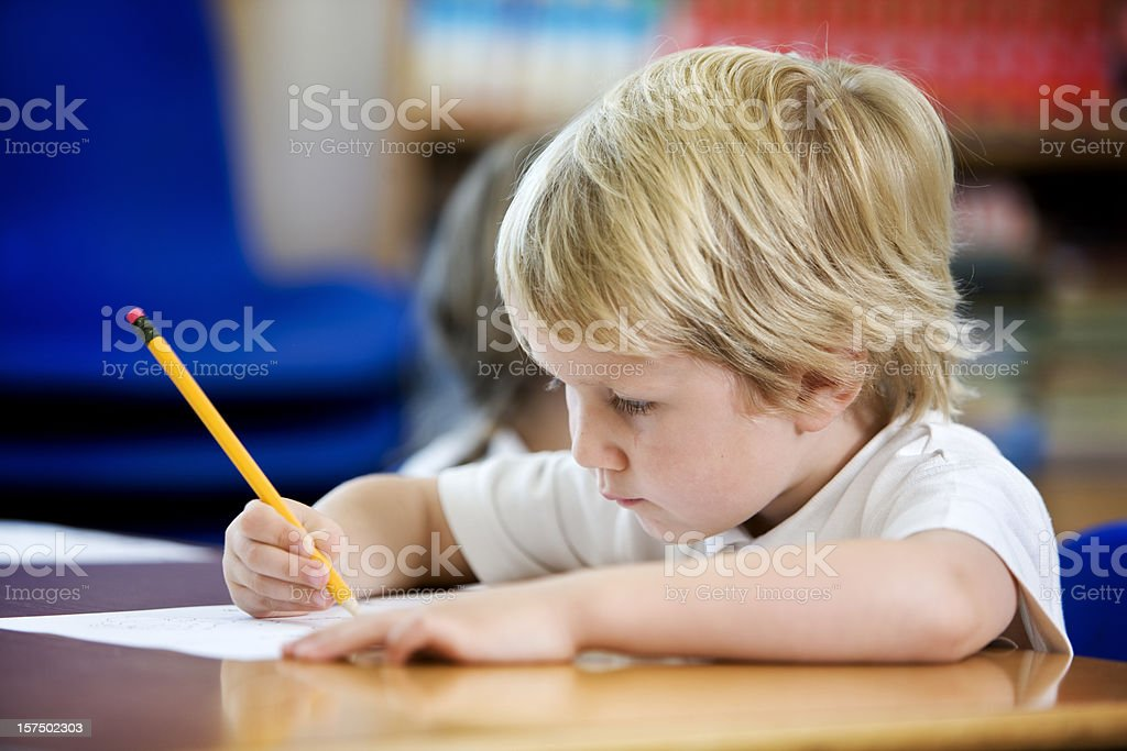 primary school: young boy concentrating on learning to write royalty-free stock photo