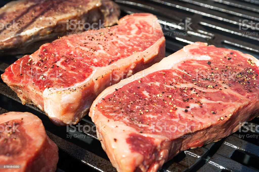 Prime New York Strip steaks on barbecue stock photo