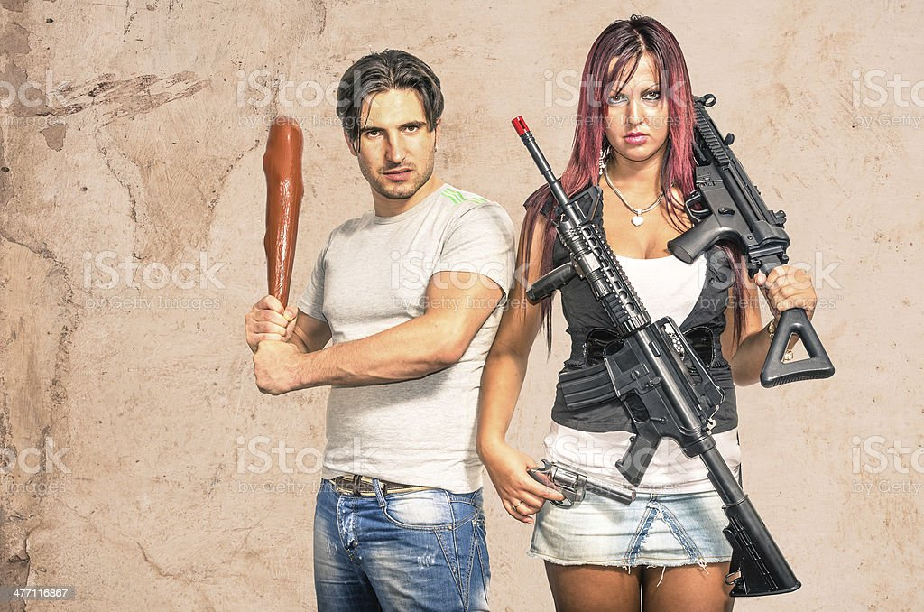 Primitive man and modern woman with weapons - Funny Couple stock photo