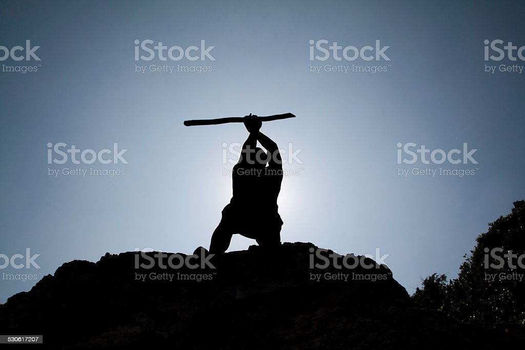 Primitive man silhouette against the sun. stock photo