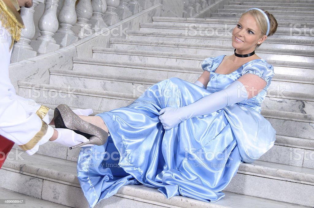 Prince Charming helping Cinderella to try her shoe on stock photo