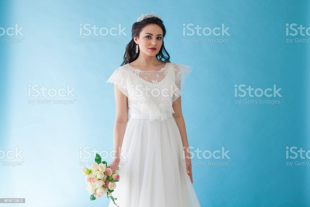 Princess Bride in a white dress with a Crown on a blue background stock photo