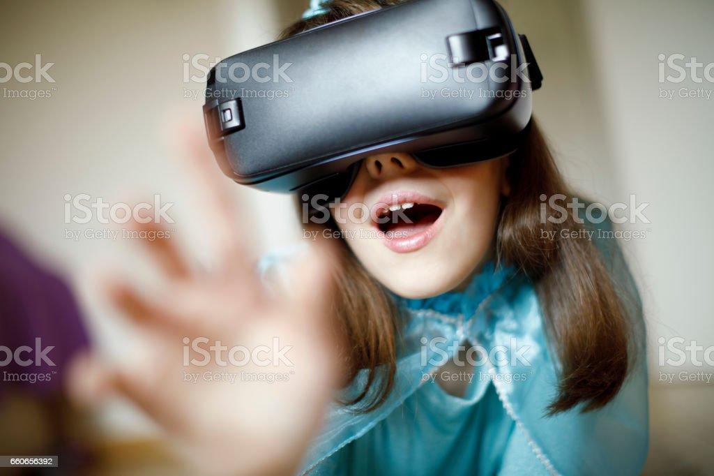 Princess girl using virtual reality glasses stock photo