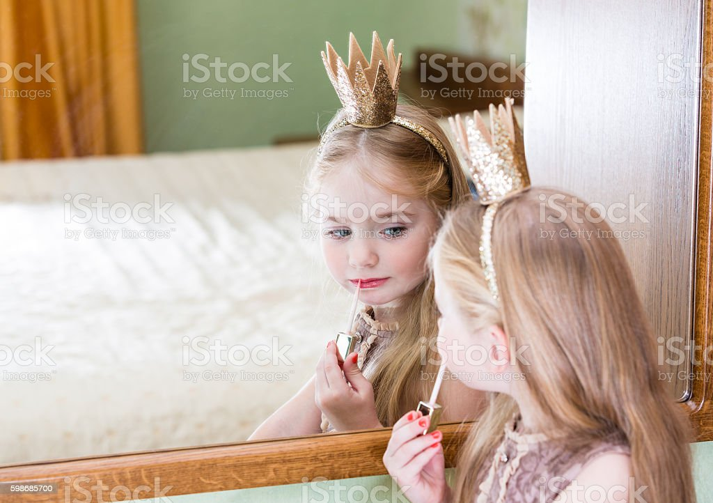 princess little girl painting makeup lipstick on mirror stock photo
