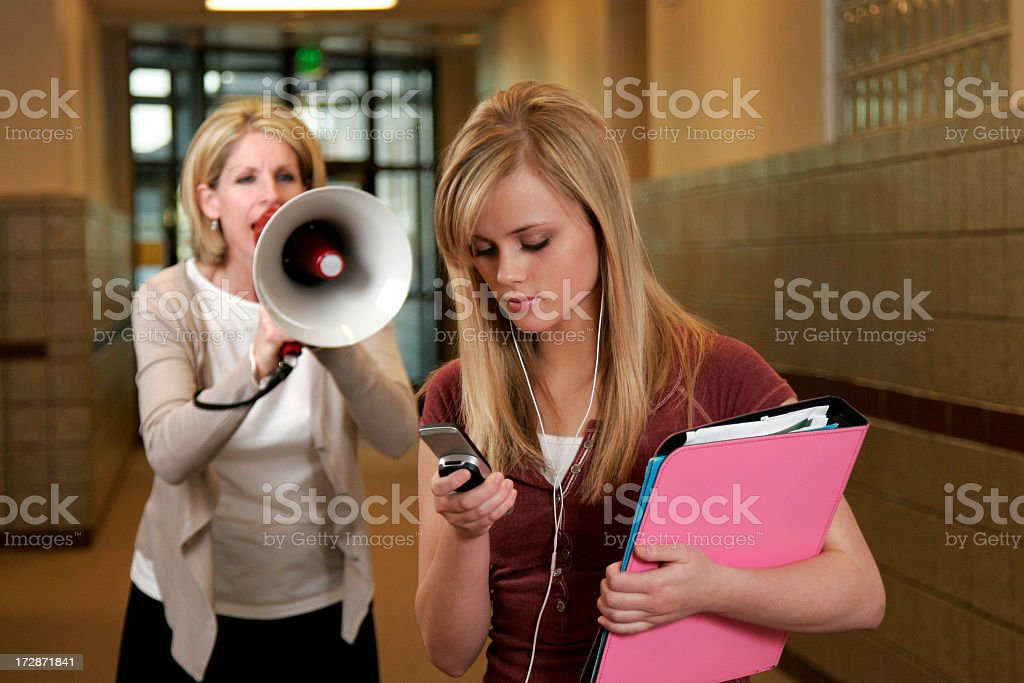Principal with mega phone yelling at student using her phone royalty-free stock photo