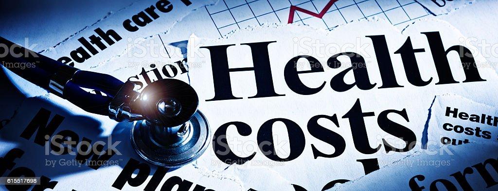 Print headlines on health costs with stethoscope stock photo