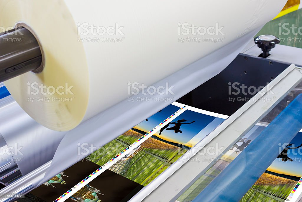 Print sheet-fed paper feeder unit. Poster laminator stock photo
