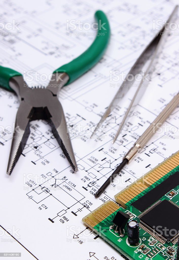 Printed circuit board and precision tools on diagram of electronics stock photo