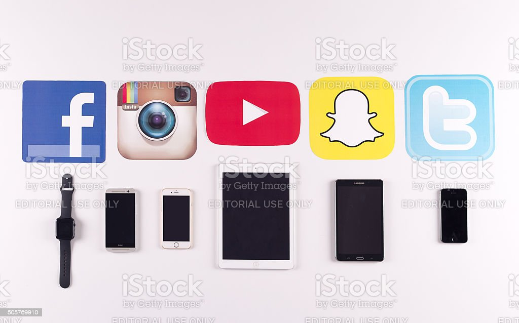 Printed Paper Social Media Logos on Desk with Mobile Devices stock photo