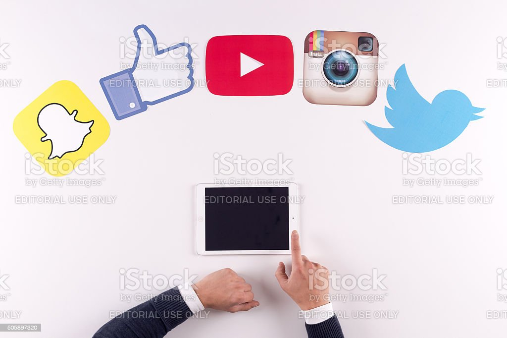 Printed Paper Social Media Logos on Desk with User stock photo