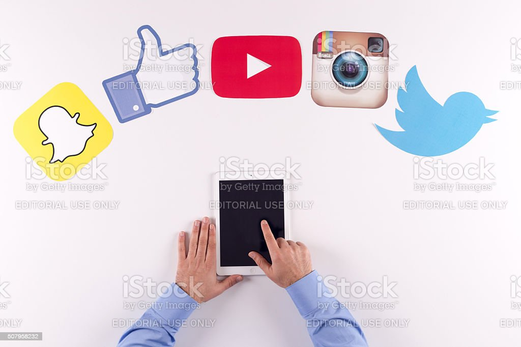 Printed Paper Social Media Logos on Desk with Users stock photo