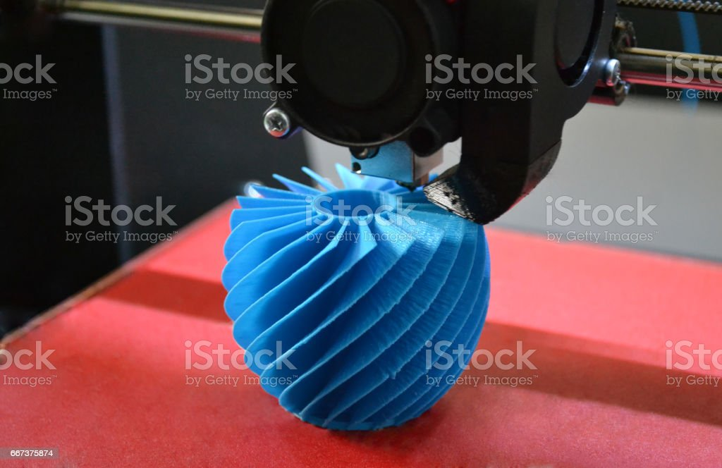 3D printer working and creating an object from the hot molten plastic stock photo