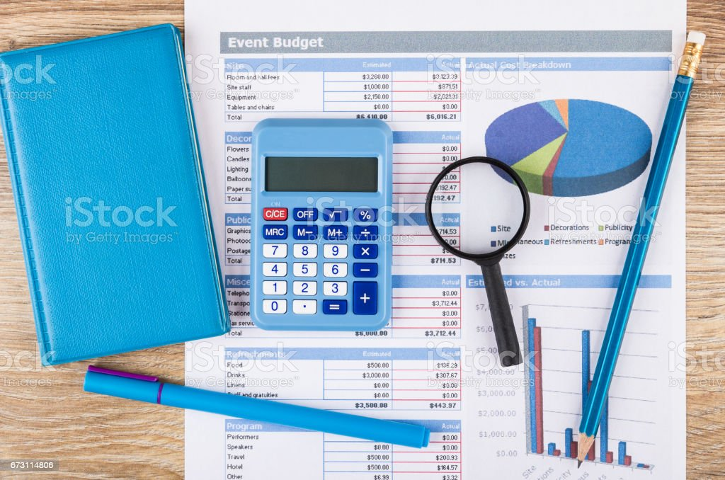 Printout of event budget, calculator, notepad, magnifying glass and pen stock photo
