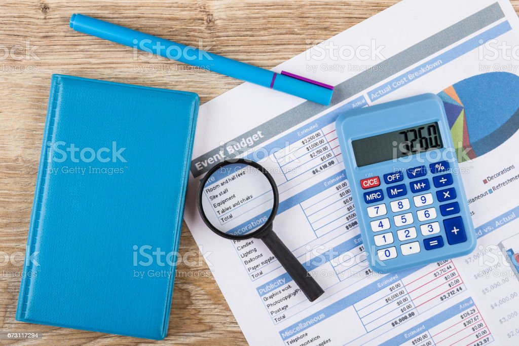 Printout of event budget, calculator, notepad, pen and magnifying glass stock photo