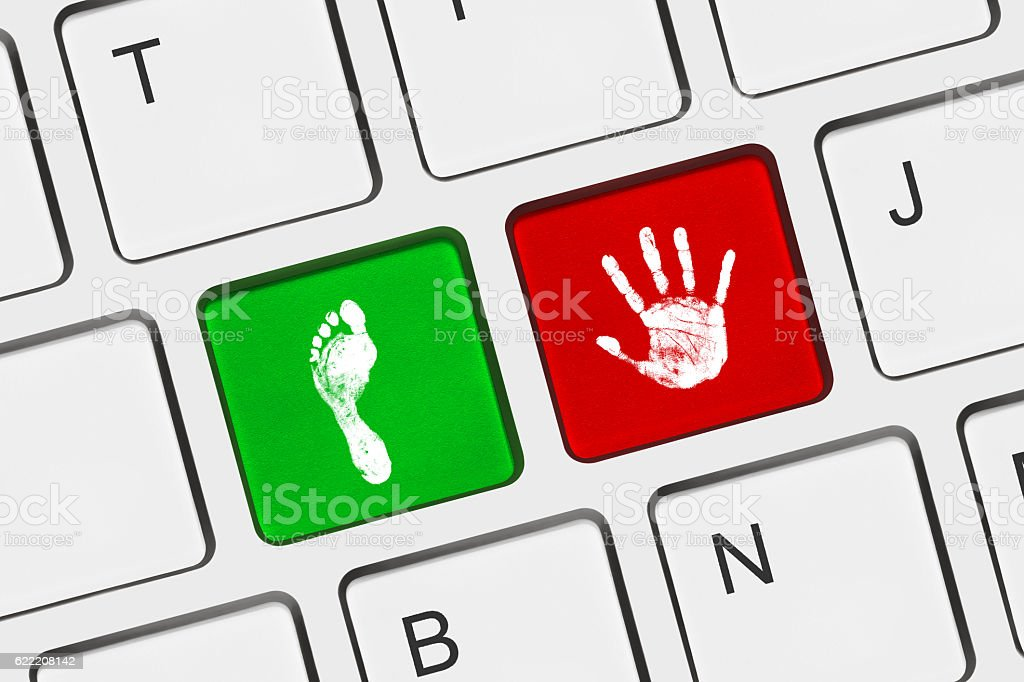 Printout of hand and foot on computer keys stock photo