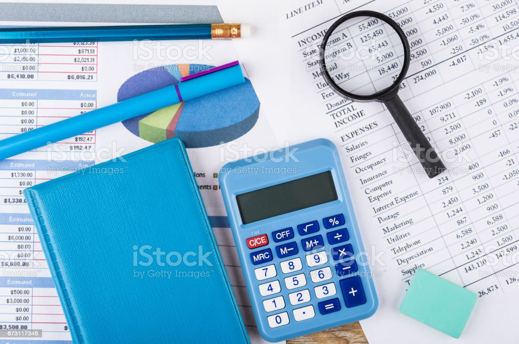 Printouts of financial information, notepad, calculator and magnifying glass stock photo