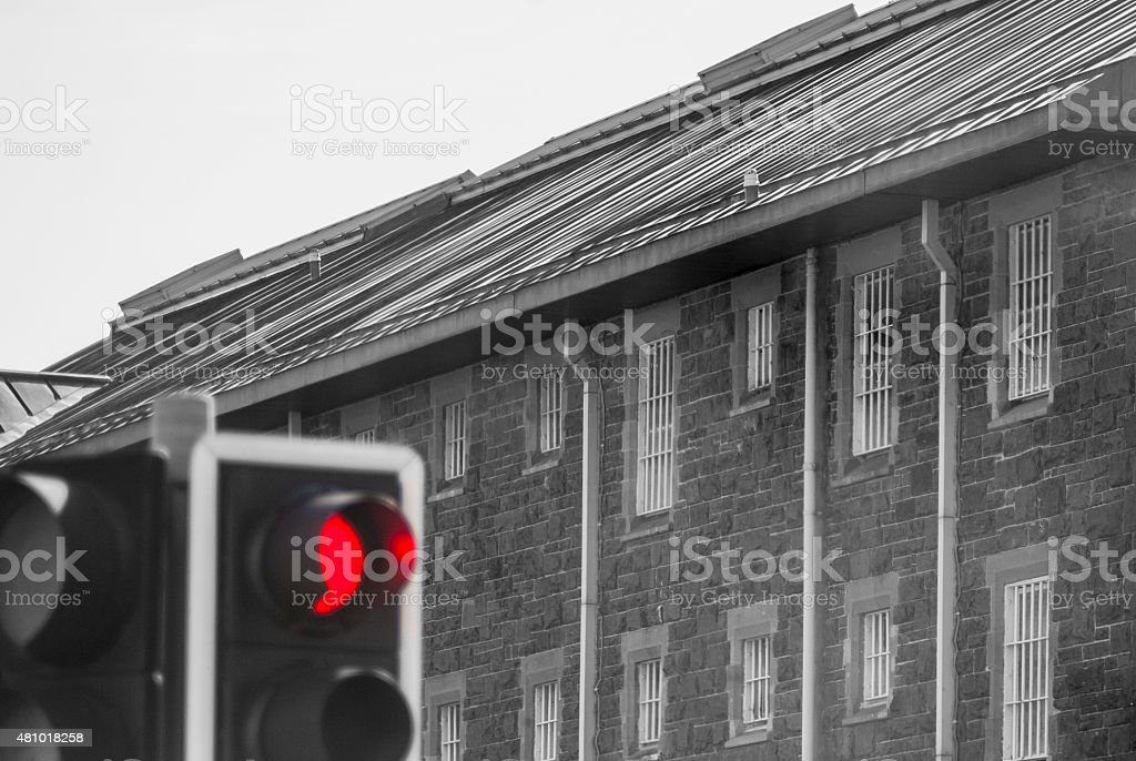 Prison and Red Stop Traffic light. Mainly black and white. stock photo