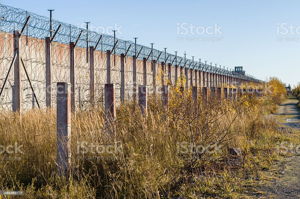 Prison wall and sharp wire barbs coiled stock photo