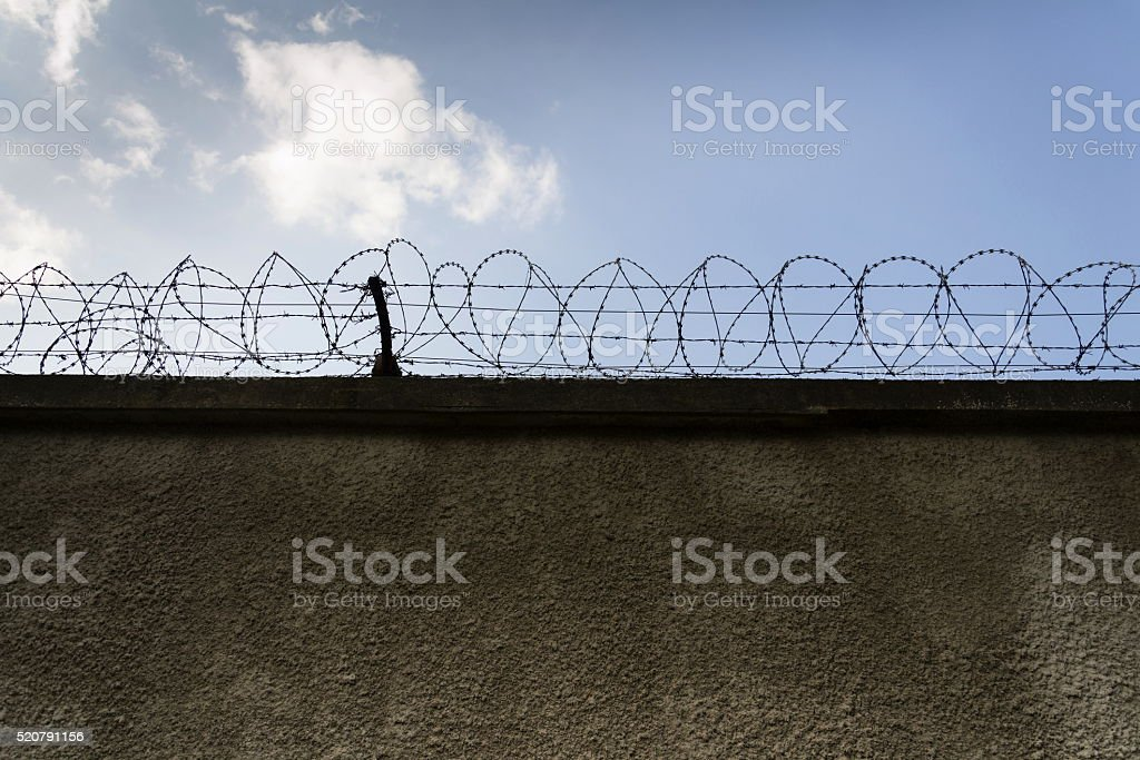 Prison wall barbed wire fence with blue sky background stock photo